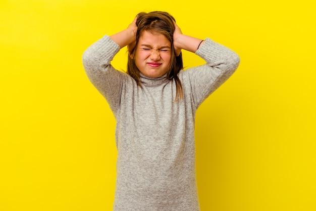 Маленькая кавказская девочка изолирована на желтом покрытии ушей руками, пытаясь не слышать слишком громкий звук.