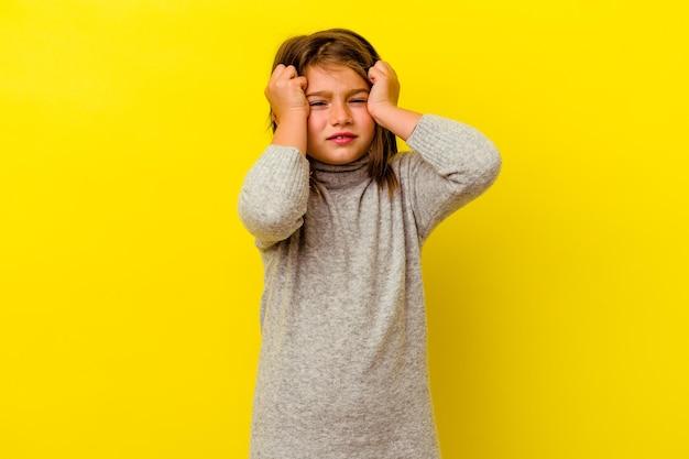 Маленькая кавказская девушка изолирована на желтом плаче, недовольна чем-то, концепцией агонии и замешательства.