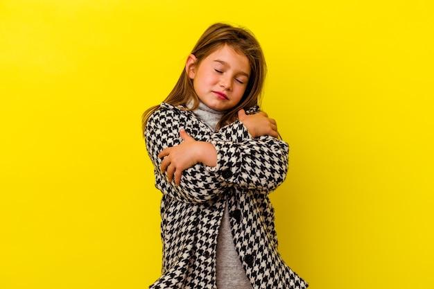 Маленькая кавказская девушка изолирована на желтых объятиях, беззаботно улыбается и счастлива.