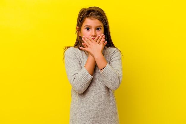 노란색에 고립 된 어린 백인 소녀는 손으로 입 취재 충격.