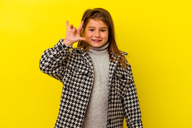 革命の概念として角のジェスチャーを示す黄色で隔離された小さな白人の女の子。