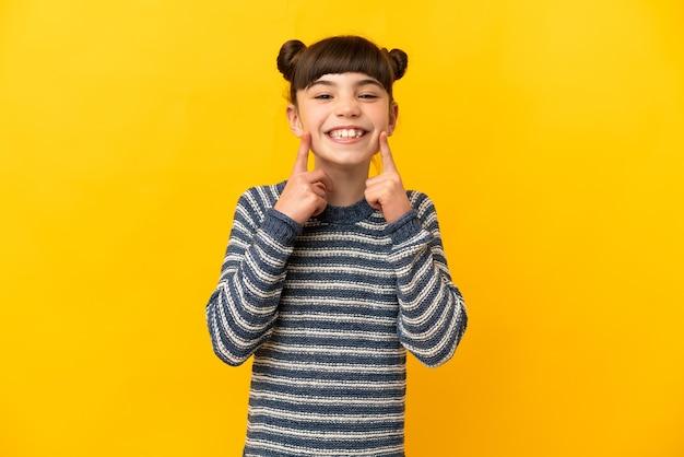 Маленькая кавказская девушка изолирована на желтом, улыбаясь счастливым и приятным выражением лица