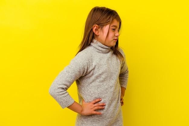 Маленькая кавказская девочка, изолированных на желтом, страдает от боли в спине.