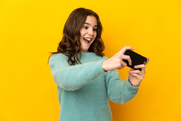 휴대 전화를 가지고 노는 노란색 표면에 고립 된 어린 백인 소녀