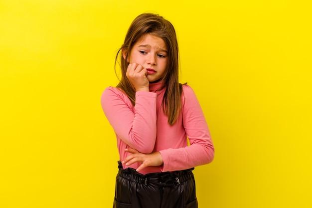 Маленькая кавказская девушка изолирована на желтой стене, кусая ногти, нервная и очень взволнованная.
