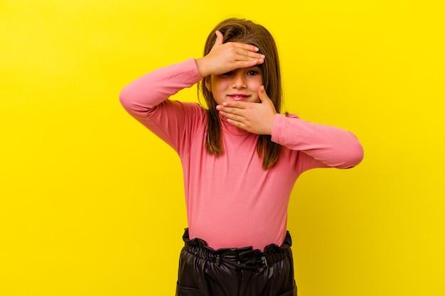 Маленькая кавказская девочка, изолированная на желтой стене, моргает пальцами в камеру, смущенно закрывая лицо.