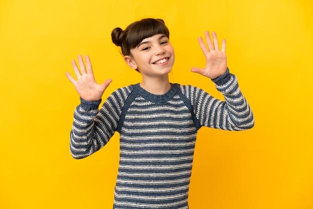 Маленькая кавказская девушка изолирована на желтой стене, считая десять пальцами