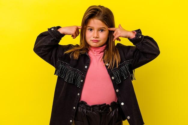 노란색 벽에 고립 된 어린 백인 소녀는 머리를 가리키는 집게 손가락을 유지하는 작업에 집중했다.