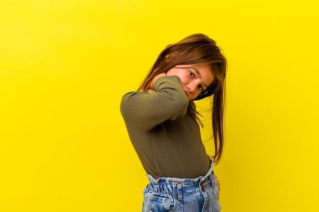 Маленькая кавказская девушка изолирована на желтой стене с болью в шее из-за стресса, массируя и касаясь ее рукой.