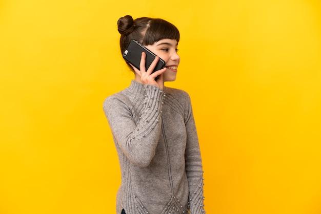 누군가와 휴대 전화로 대화를 유지하는 노란색 벽에 고립 된 어린 백인 소녀