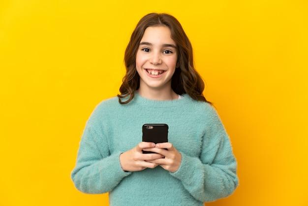 黄色い壁に孤立した白人の少女が正面を見て、携帯電話を使用しながら笑っている