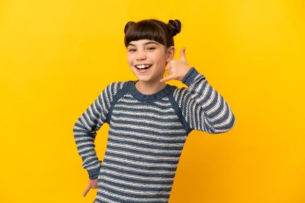 Маленькая кавказская девушка, изолированные на желтой стене, делая телефонный жест. перезвони мне знак