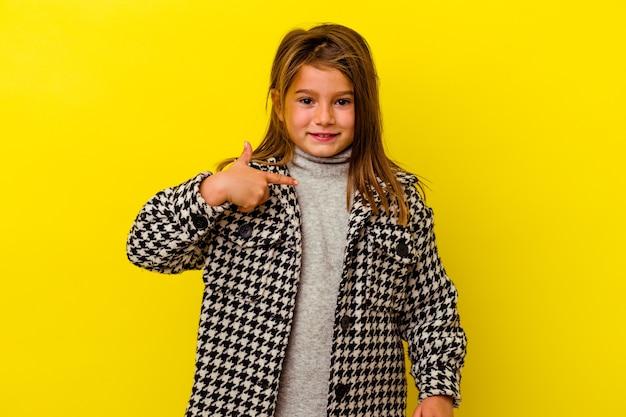 자랑스럽고 자신감, 셔츠 복사 공간을 손으로 가리키는 노란색 벽 사람에 고립 된 어린 백인 소녀
