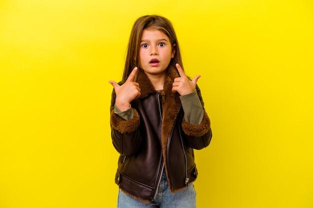 열린 된 입으로 거꾸로 가리키는 노란색 벽에 고립 된 어린 백인 소녀.