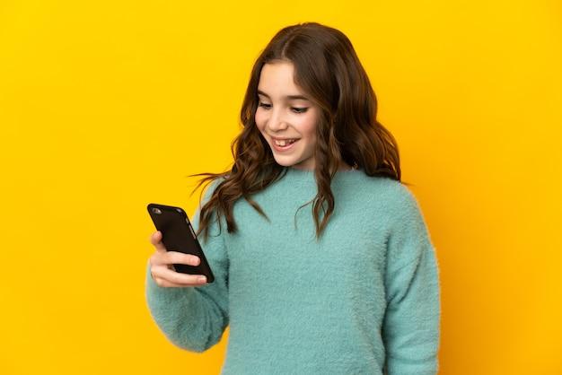 모바일로 메시지 또는 이메일을 보내는 노란색 벽에 고립 된 어린 백인 소녀