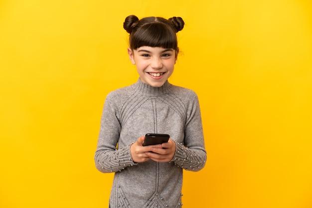 Маленькая кавказская девушка изолирована на желтой стене, отправляя сообщение с мобильного телефона