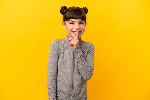 Маленькая кавказская девушка изолирована на желтой стене, показывая знак жеста молчания, кладя палец в рот