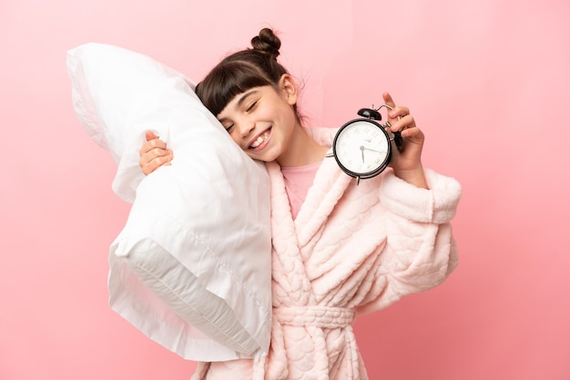 Little caucasian girl isolated in pajamas and holding clock and pillow