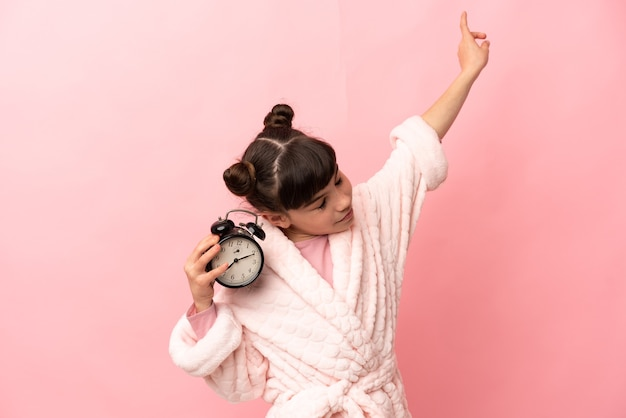 Little caucasian girl isolated in pajamas and holding clock with happy expression