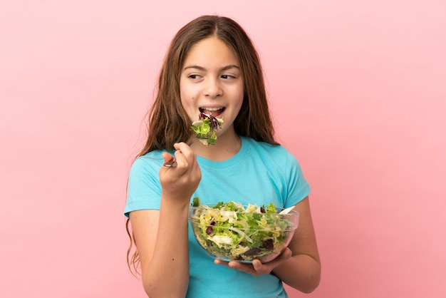 Little caucasian girl isolated on pink background holding a bowl of salad with happy expression