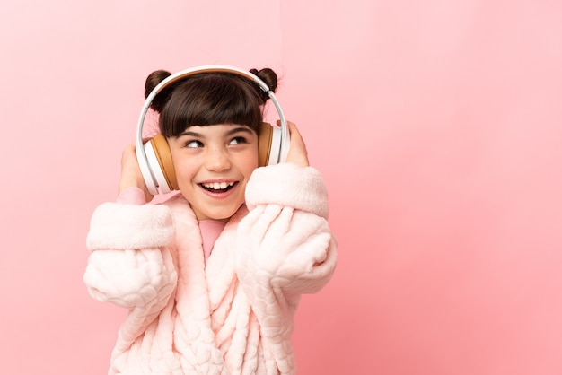 Little caucasian girl isolated on pink background in pajamas and holding a pillow and listening music