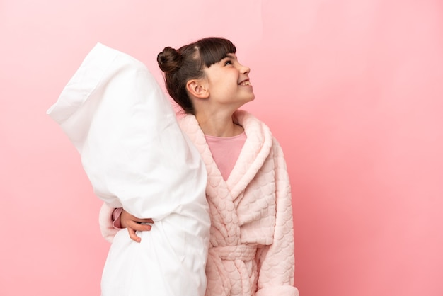Little caucasian girl isolated on pink background in pajamas and looking up while smiling