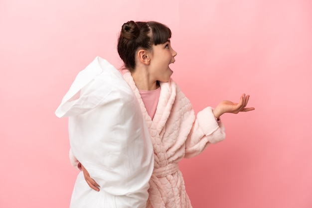 Little caucasian girl isolated on pink background in pajamas with surprise facial expression