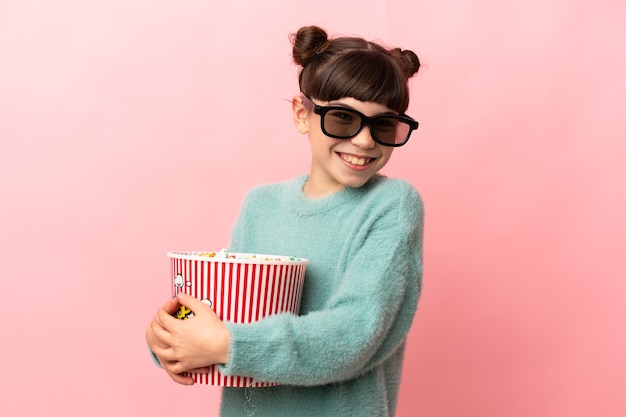Little caucasian girl isolated on pink background with 3d glasses and holding a big bucket of popcorns