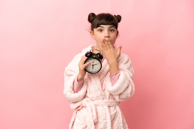 Little caucasian girl isolated on pink in pajamas and holding clock with surprised expression