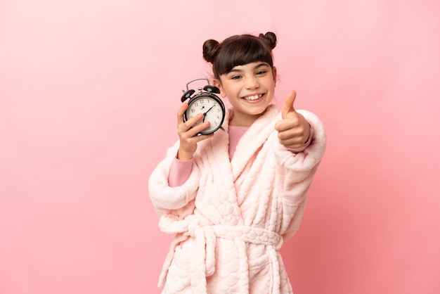 Little caucasian girl isolated on pink in pajamas and holding clock with thumb up