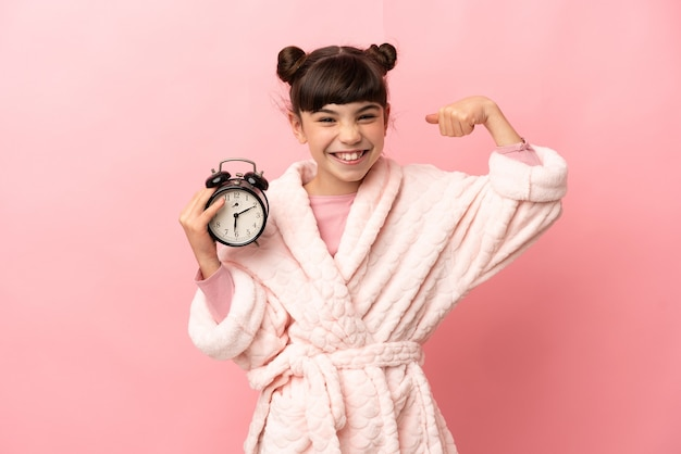 Little caucasian girl isolated on pink wall in pajamas and holding clock while doing strong gesture