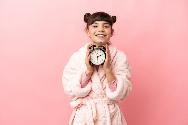 Little caucasian girl isolated on pink wall in pajamas and holding clock with happy expression