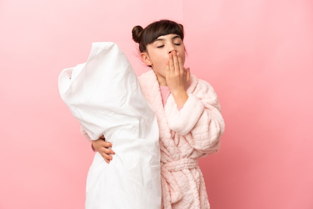 Little caucasian girl isolated on pink wall in pajamas and holding a pillow and yawning