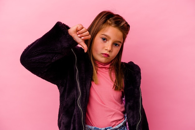 Little caucasian girl isolated on pink wall  showing a dislike gesture, thumbs down. disagreement concept.