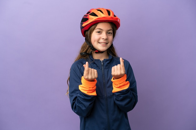 Little caucasian girl isolated on purple background making money gesture
