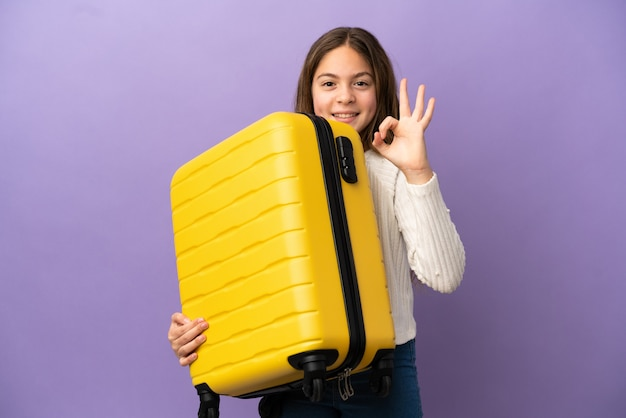 Little caucasian girl isolated on purple background in vacation with travel suitcase and making ok sign