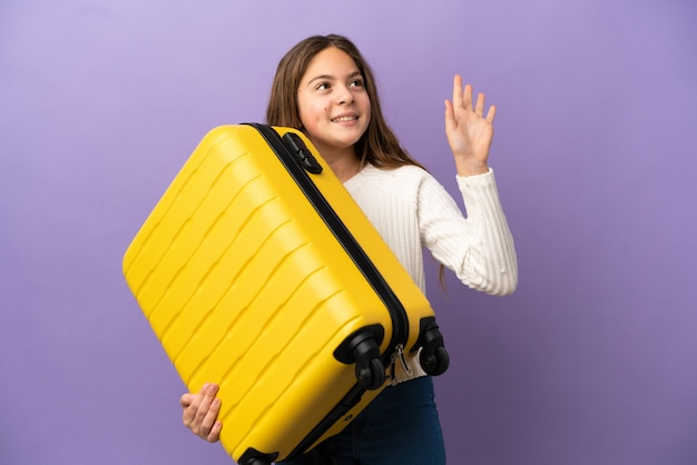 Little caucasian girl isolated on purple background in vacation with travel suitcase and saluting
