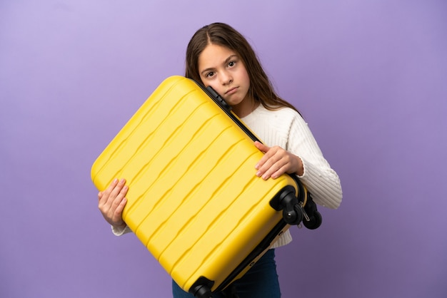 Little caucasian girl isolated on purple background in vacation with travel suitcase and unhappy