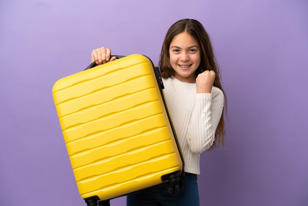 Little caucasian girl isolated on purple background in vacation with travel suitcase
