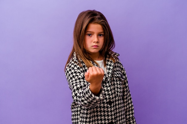 Little caucasian girl isolated on purple showing fist to camera, aggressive facial expression.