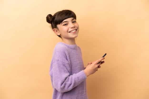 Маленькая кавказская девушка изолирована, отправляя сообщение или электронное письмо с мобильного телефона