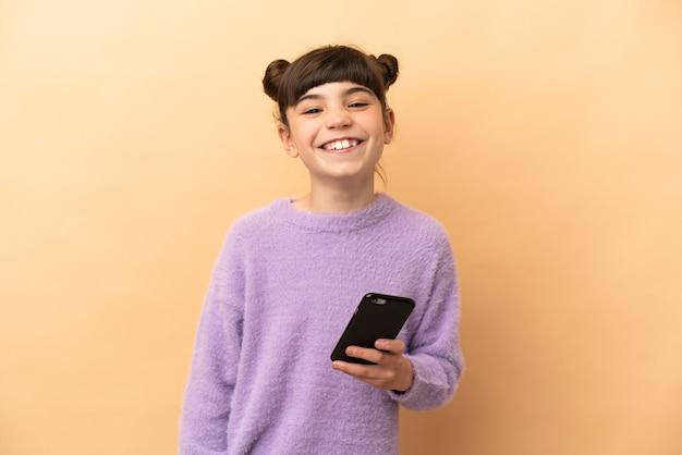 Маленькая кавказская девушка изолирована с помощью мобильного телефона