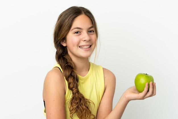 Little caucasian girl isolated on white background with an apple and happy