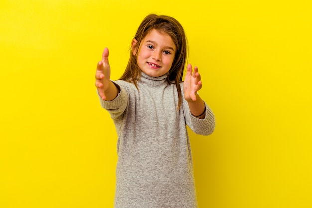 Little caucasian girl isolated on yellow background feels confident giving a hug to the camera.