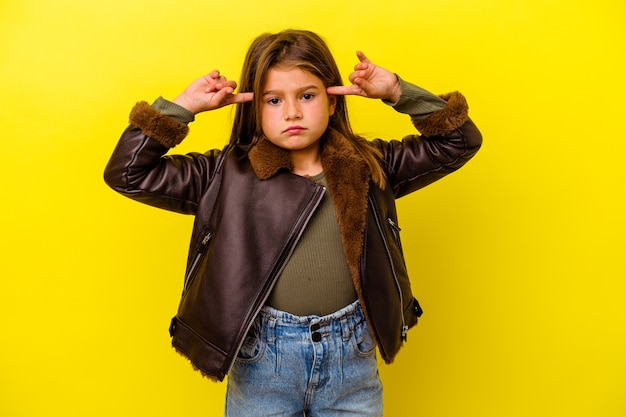 Little caucasian girl isolated on yellow background focused on a task, keeping forefingers pointing head.