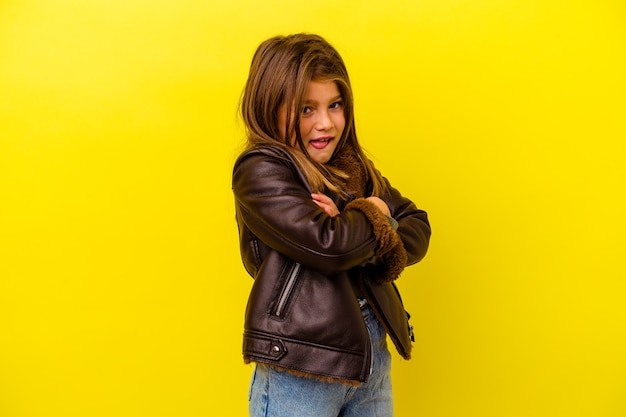 Little caucasian girl isolated on yellow background funny and friendly sticking out tongue.