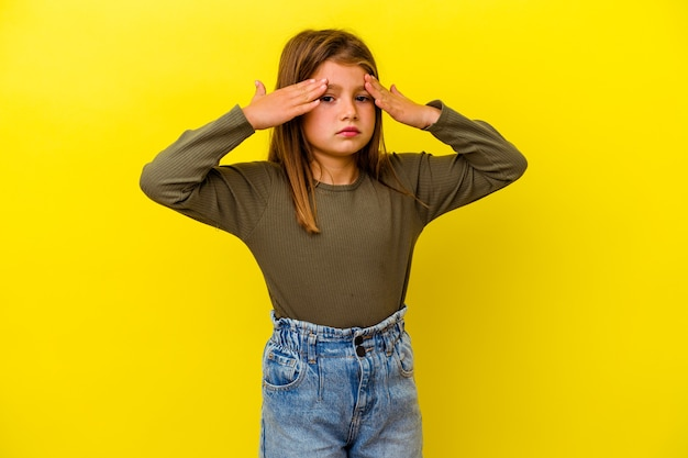 Little caucasian girl isolated on yellow background having a head ache, touching front of the face.