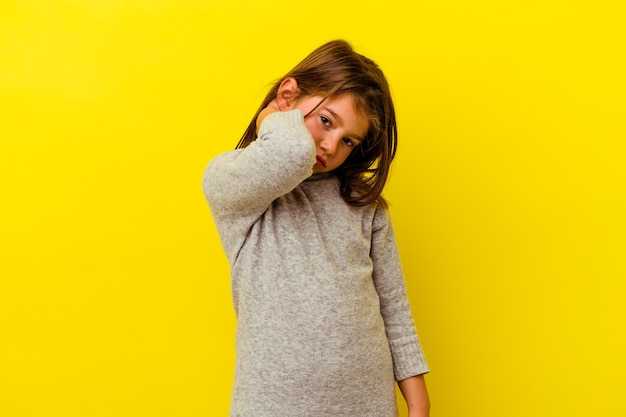 Little caucasian girl isolated on yellow background having a neck pain due to stress, massaging and touching it with hand.