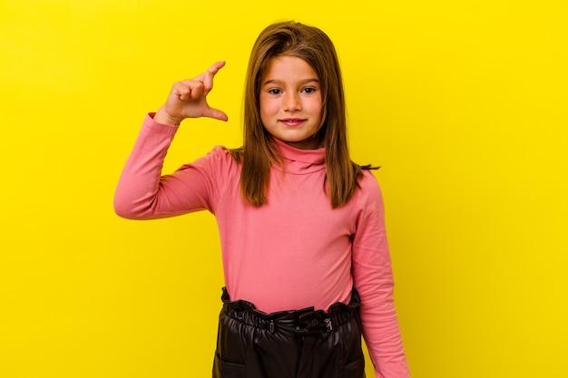 Little caucasian girl isolated on yellow background holding something little with forefingers, smiling and confident.
