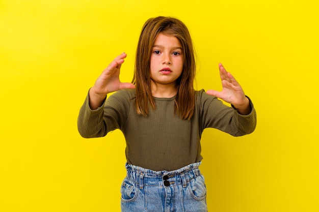 Little caucasian girl isolated on yellow background holding something with palms, offering to camera.